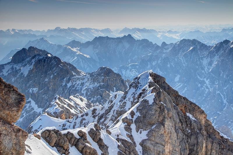 Jubilaumsgrat ridge with jagged Wetterstein / Karwendel ranges. Elevated view of snowy climbing route Jubilaumsgrat with jagged blue ridges of Wetterstein and stock photos