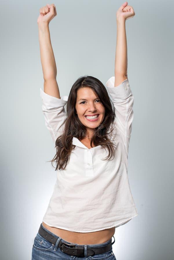 Jublande ung kvinna som hurrar hennes framgång arkivfoto