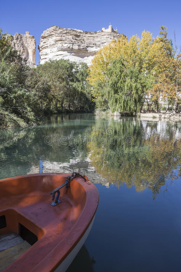Jucar river, boat of recreation in small lagoon in the central p. Art of the town, at the top of mountain limestone is situated castle of Almohad origin of the royalty free stock photo