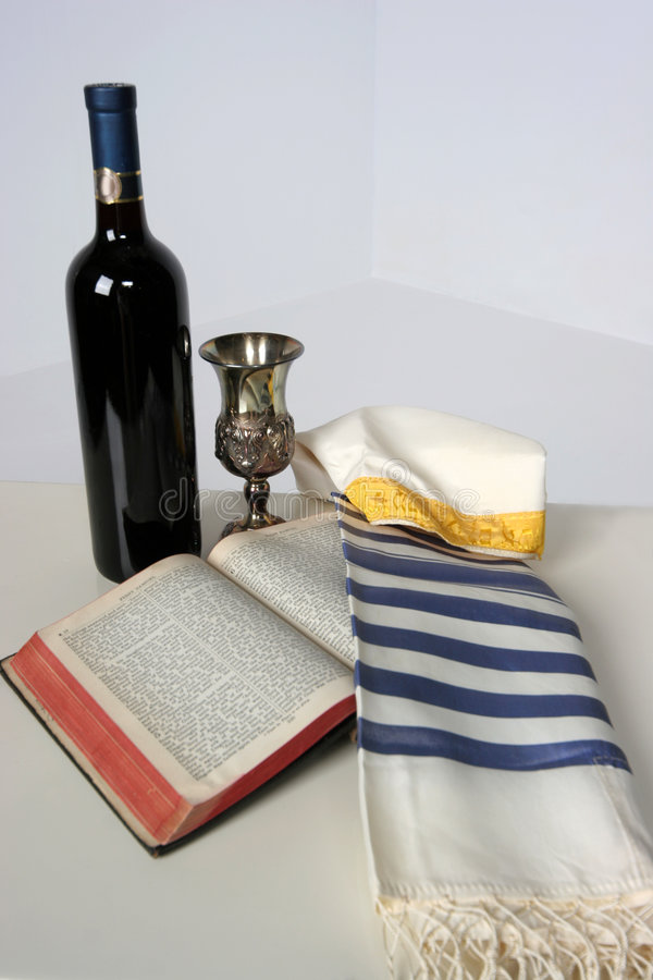 Judaica. Holy Scriptures opened with Talid resting on it Kaddish cup and a bottle of red wine royalty free stock image