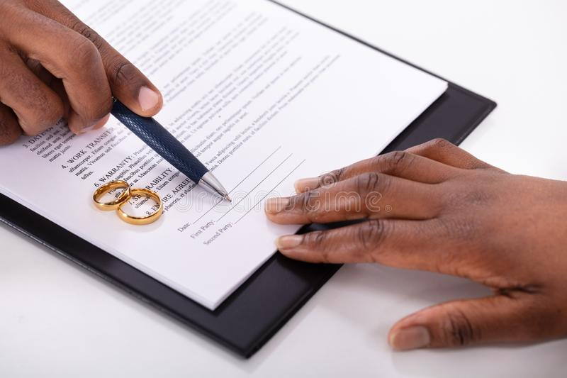 Judge Assisting Client In Filling Contract Form. With Pair Of Golden Rings stock image
