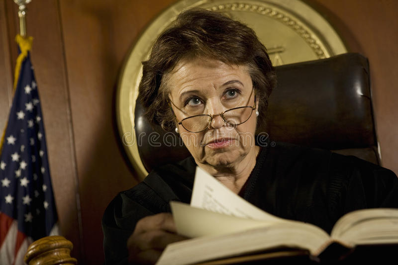 Judge With Book Looking Away In Court Room. Middle age female judge with book looking away in court room royalty free stock photos