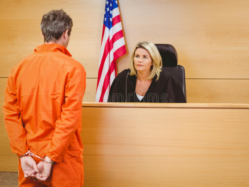 Judge and criminal speaking in front of the american flag. In the court room royalty free stock image
