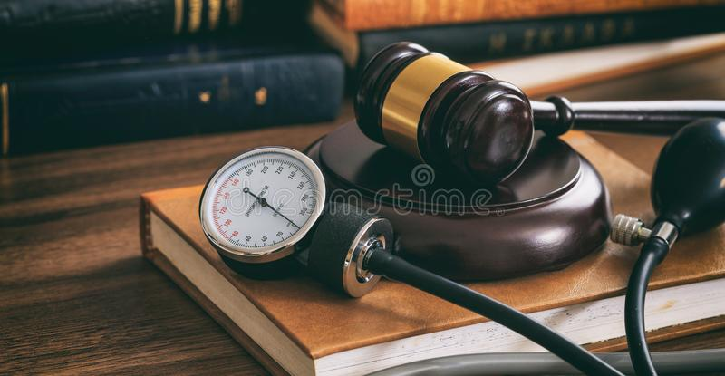Judge gavel and a blood pressure gauge on a wooden desk. Law gavel and a blood pressure gauge on a wooden desk, dark background royalty free stock photos