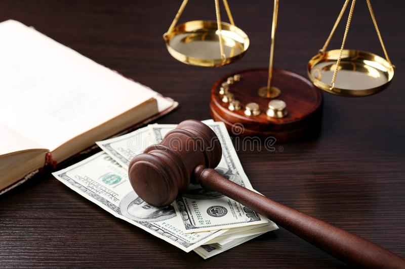 Judge gavel with dollars. Book and scales on wooden table royalty free stock photos