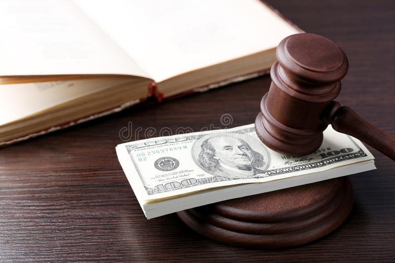 Judge gavel with dollars. And book on wooden table stock photography