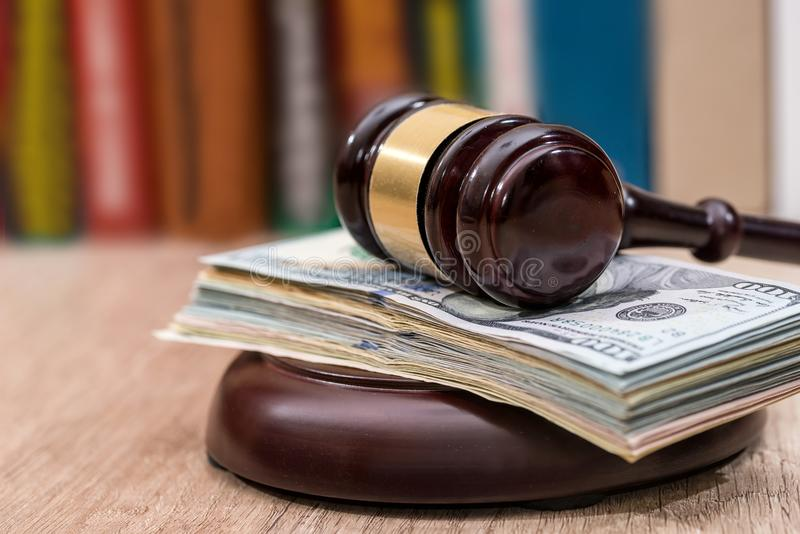 Judge gavel with dollars, books. On wooden desk close up royalty free stock image