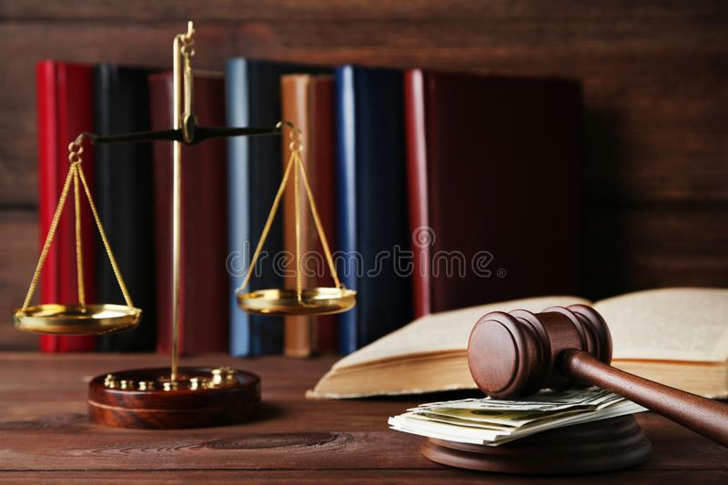 Judge gavel with dollars. Books and scales on wooden table stock images