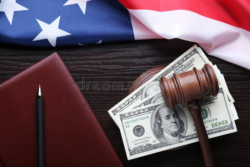 Judge gavel with dollars. American flag and book on wooden table royalty free stock photos