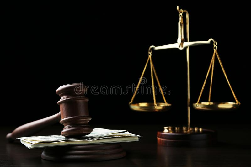Judge gavel with dollars. And scales on wooden table stock images