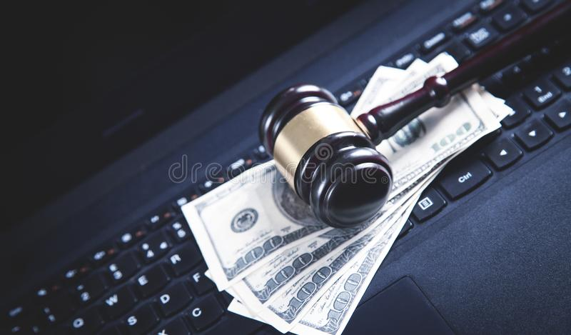 Judge gavel and dollars on a laptop. Concept of internet crime. Law and Justice stock image