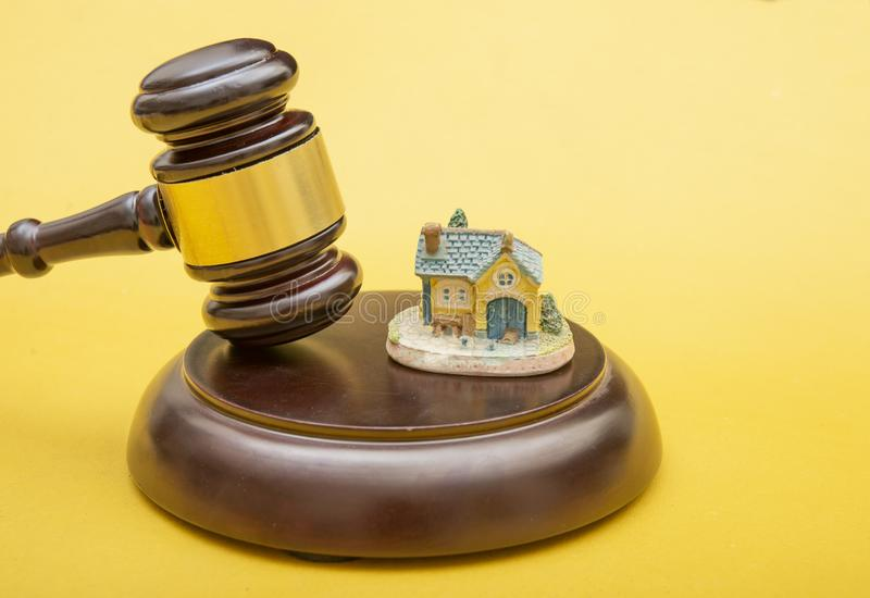 Judge gavel and home icon on yellow background, real estate and law theme royalty free stock photography