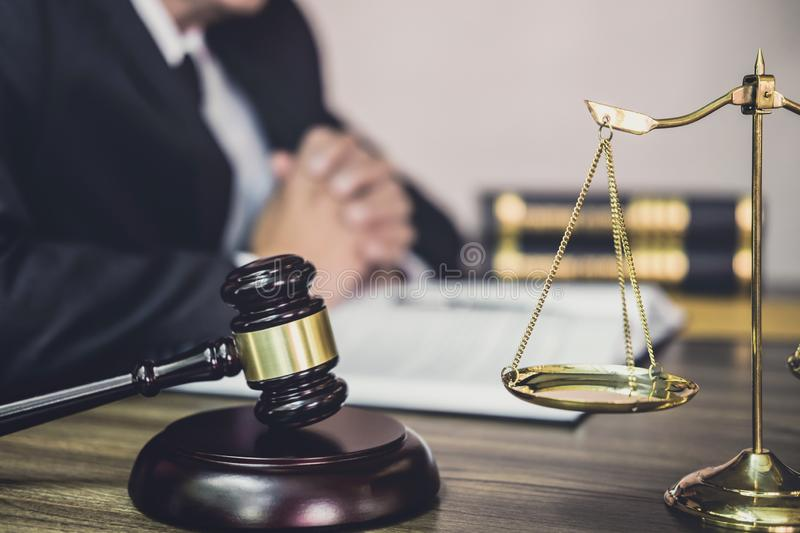 Judge gavel with Justice lawyers, Gavel on wooden table and Counselor or Male lawyer working on a documents. Legal law, advice and stock photo