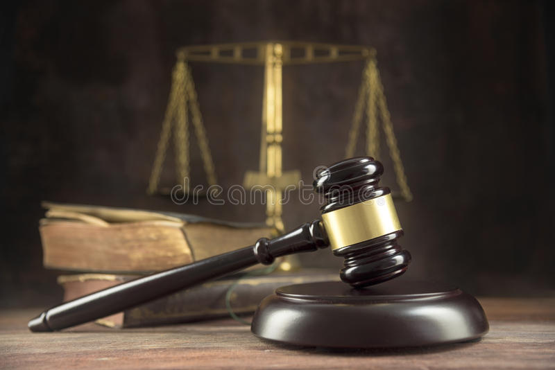Judge gavel, old books and scales on a wooden table, justice symbols for balance and power in law and court, dark background with royalty free stock image