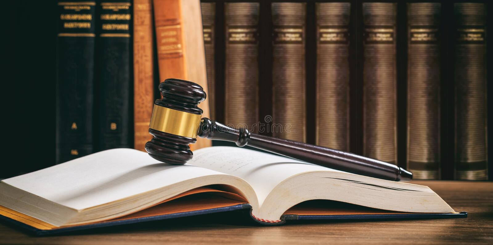 Judge gavel on an open book, wooden desk, law books background royalty free stock image