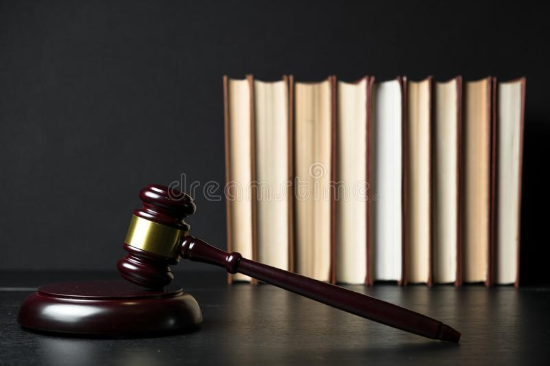 Judge gavel beside pile of books on wooden background. Judge gavel beside pile of books on black wooden background royalty free stock photos