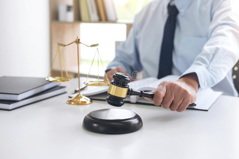 Judge gavel with scales of justice, male lawyers working having stock photo