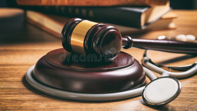 Judge gavel and a stethoscope on a wooden desk. Law gavel and a stethoscope on a wooden desk, dark background stock photography