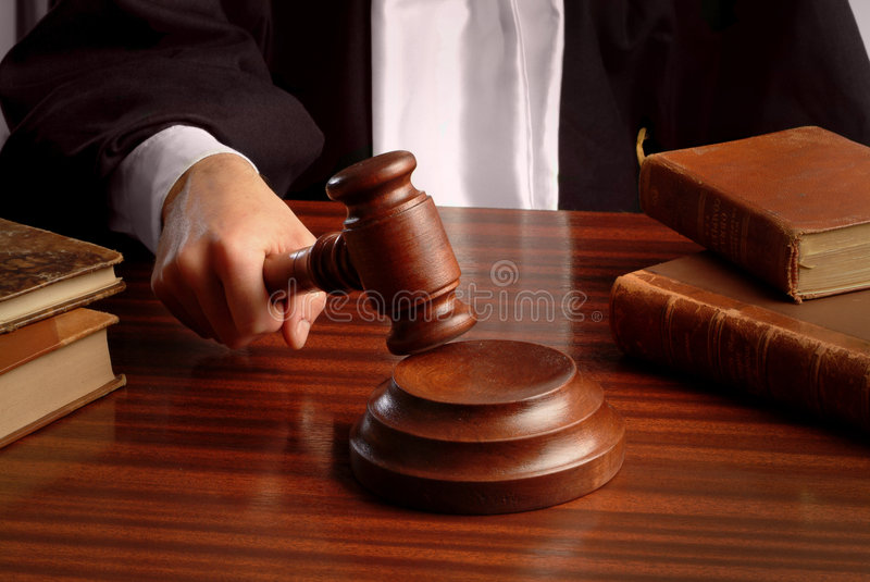 Judge hand with gavel. A judge hand striking a gavel over a table