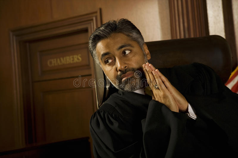 Judge With Hands Clasped Looking Away In Court Room. Thoughtful male judge with hands clasped looking away in court room stock photo