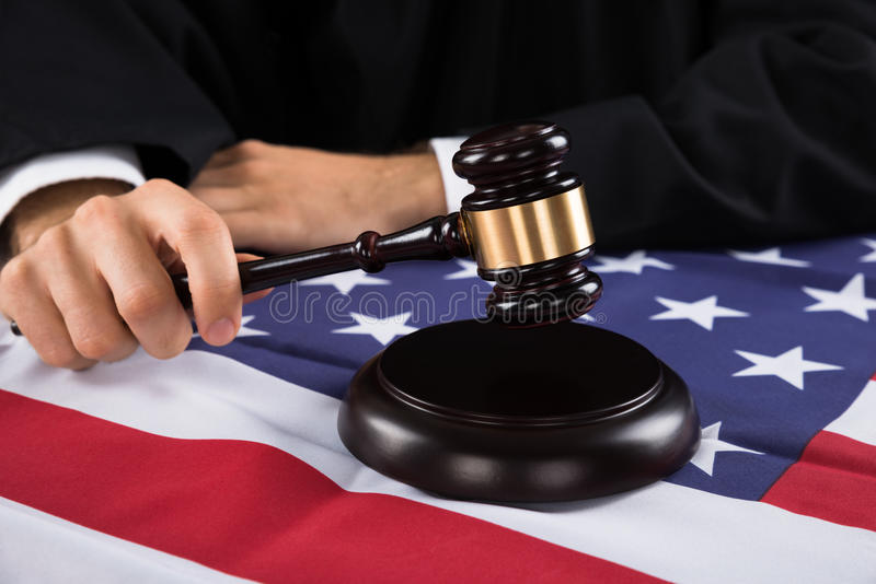 Judge Hands With Gavel And American Flag. Close-up Of Judge Hands With Gavel And American Flag At Desk stock photo