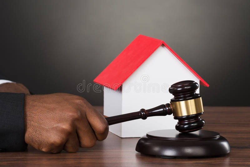 Judge Hands Hitting Gavel With House Model stock images