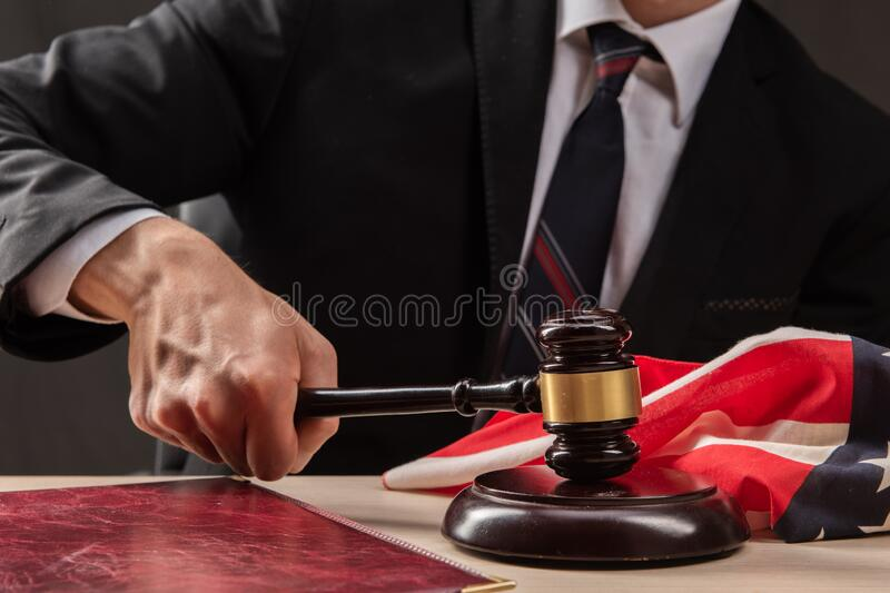 Judge hits the table with hammer. In the courtroom, the judge convicted lawyer. Judge`s gavel in hand royalty free stock photo