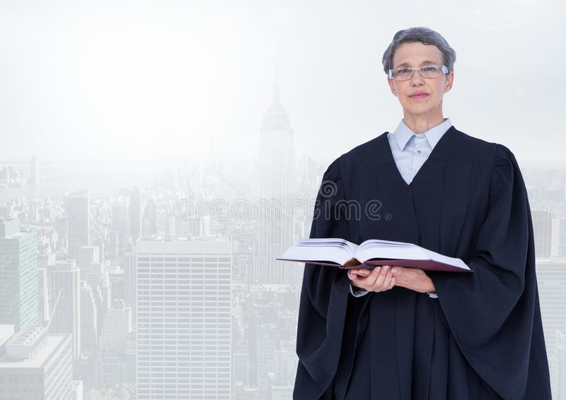 Judge holding book in front of bright city royalty free stock photography