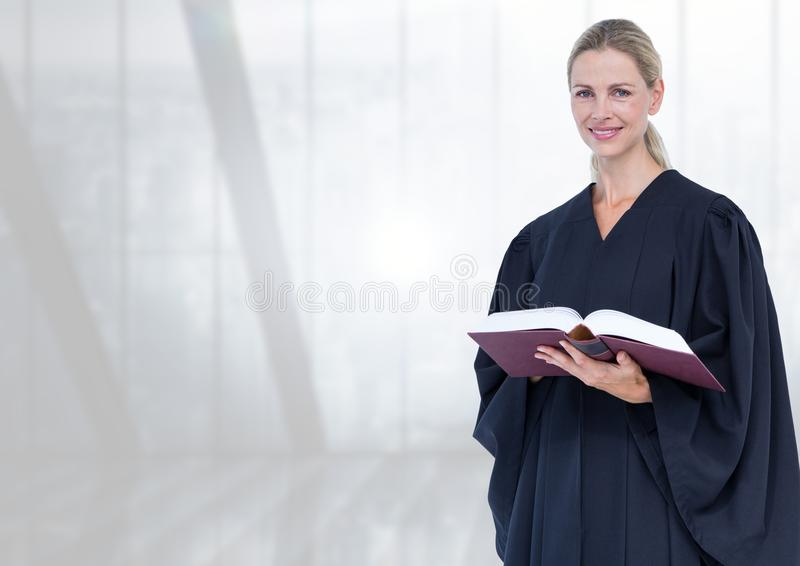 Judge holding book in front of bright windows stock photos
