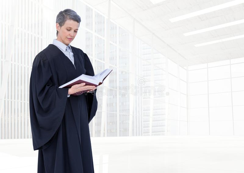 Judge holding book in front of bright windows royalty free stock images
