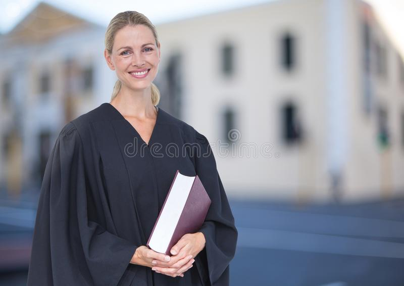 Judge holding book in front of building royalty free stock photo