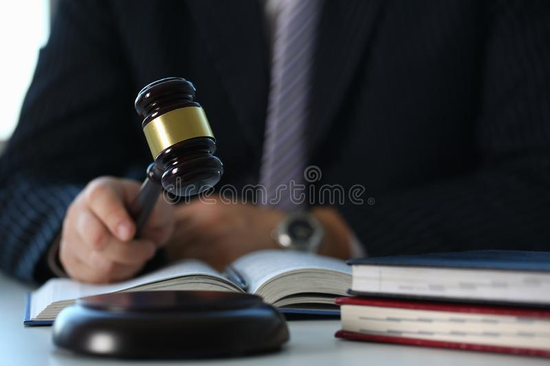 Judge holding hammer in hand lies. On table in debate room for fair judgments economic notions of violations legal system fraud and punishment royalty free stock photo