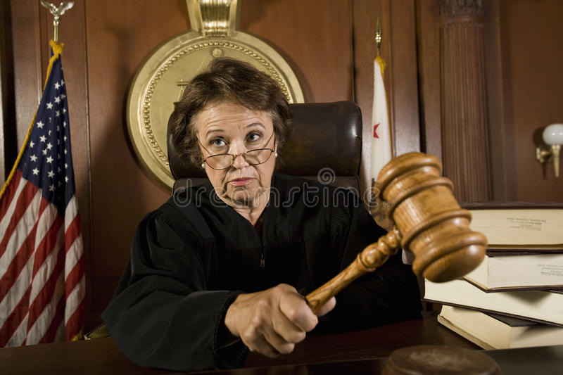 Judge Knocking A Gavel. Female judge knocking a gavel in courtroom royalty free stock image