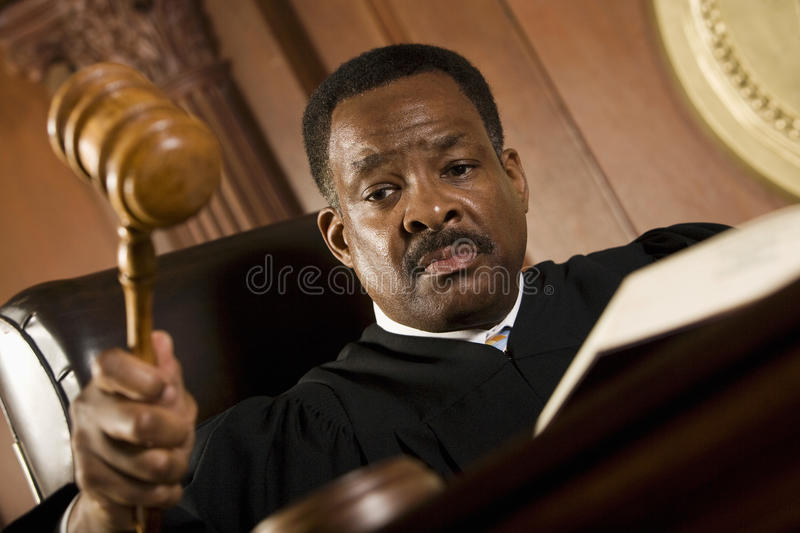 Judge Knocking Gavel In Courtroom. Serious middle aged judge knocking a gavel royalty free stock photography