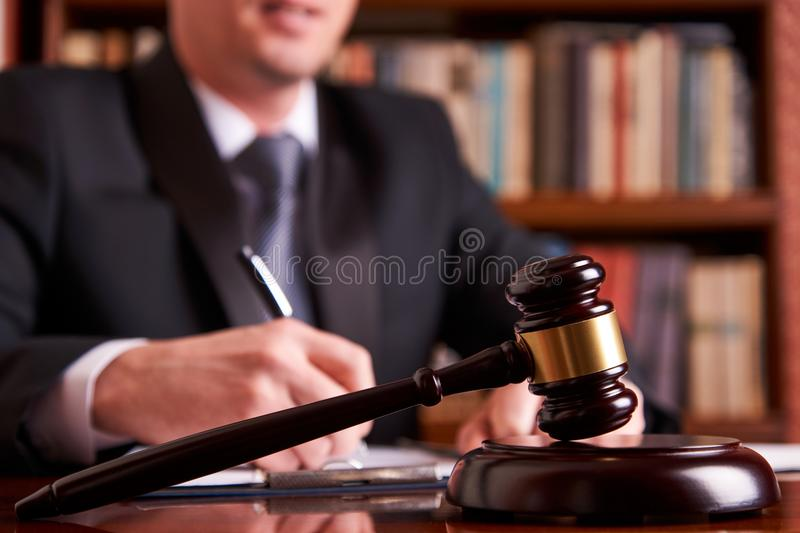 Judge or lawyer working with agreement. In courtroom theme. Justice and Law concept with judge`s gavel on wooden table with law books on background royalty free stock photo