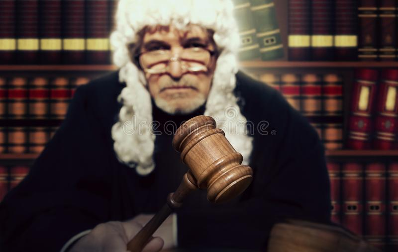 Male judge in a courtroom striking the gavel royalty free stock photos
