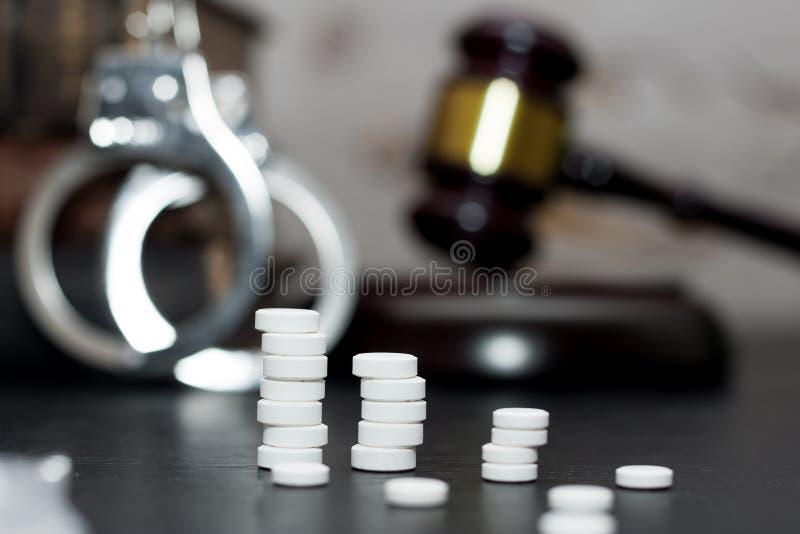 Judge& x27 ; marteau de s avec les menottes, drogues sur la table en bois images libres de droits
