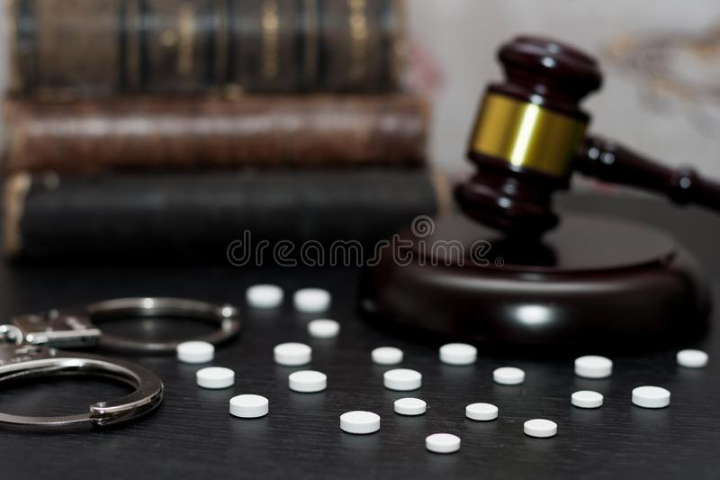 Judge& x27 ; marteau de s avec les menottes, drogues sur la table en bois photo libre de droits