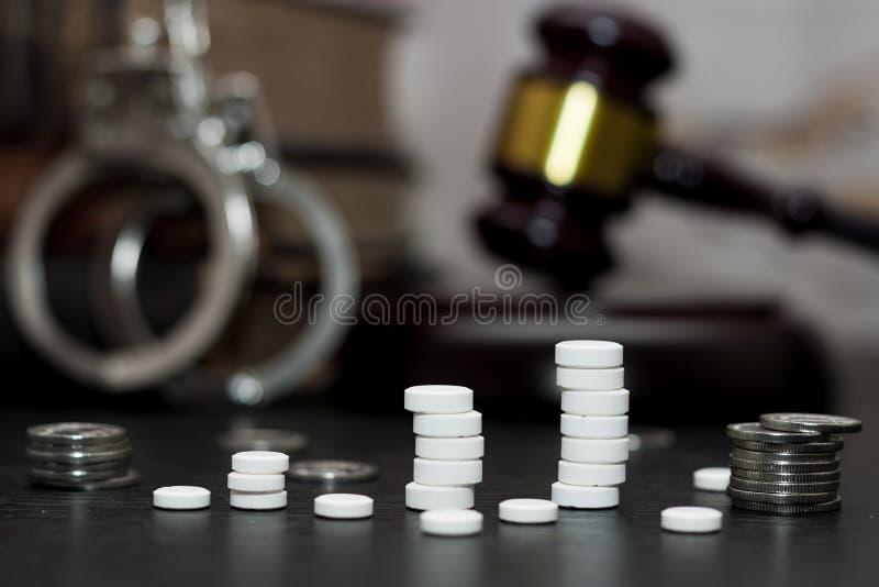 Judge& x27 ; marteau de s avec les menottes, drogues sur la table en bois photographie stock libre de droits