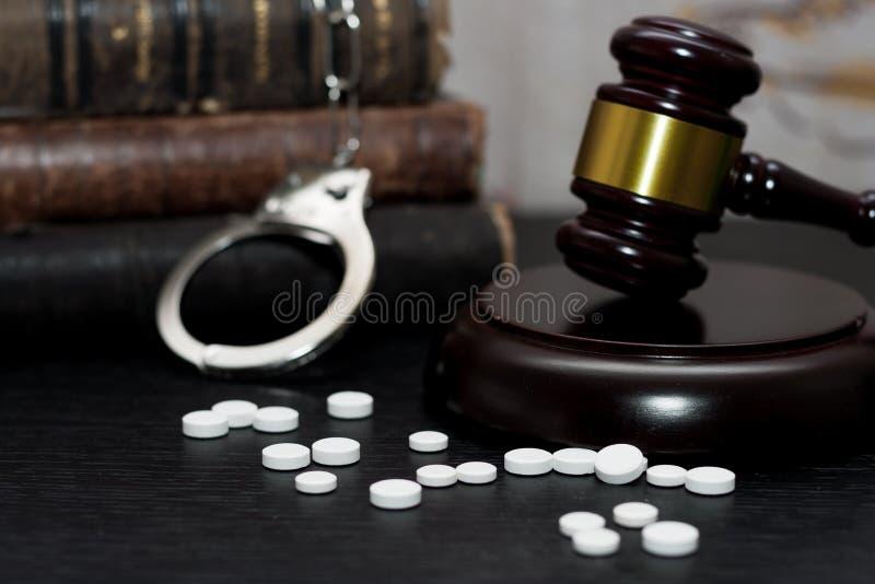 Judge& x27 ; marteau de s avec les menottes, drogues sur la table en bois photo stock