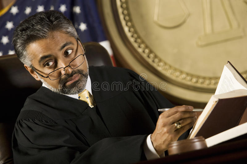 Judge Noting Important Points In Courtroom. Middle aged male judge noting important points in the courtroom stock photo