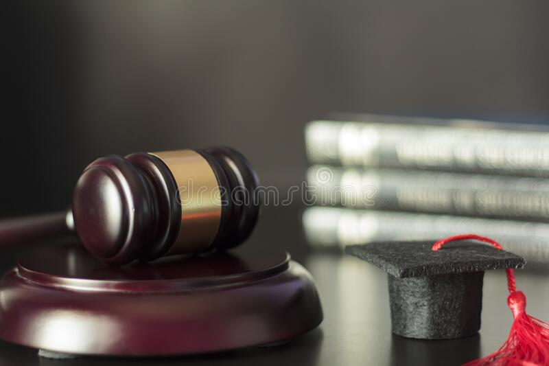 Judge`s gavel and graduation cap with stack of books on the background royalty free stock images