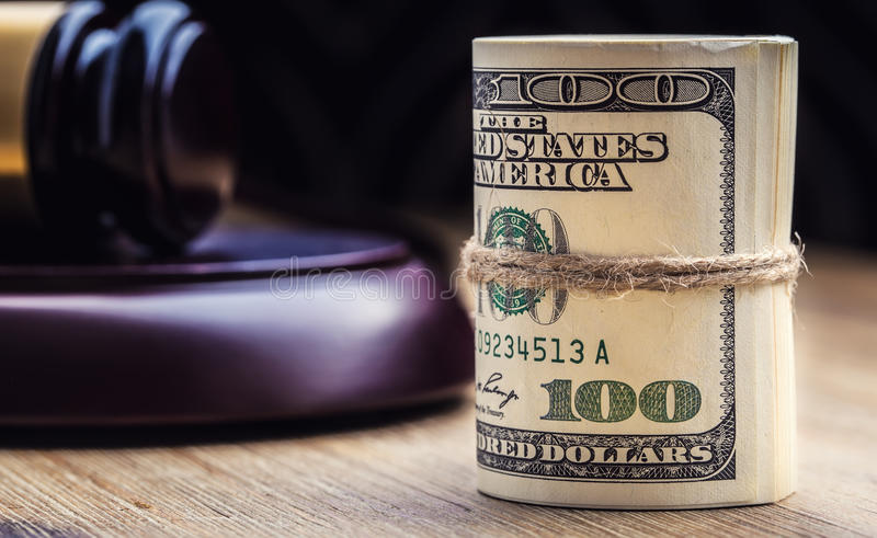 Judge`s hammer gavel. Justice dollars banknotes and usa flag in the background. Court gavel and rolled banknotes. Still life of a bribery, corruption in the US stock images
