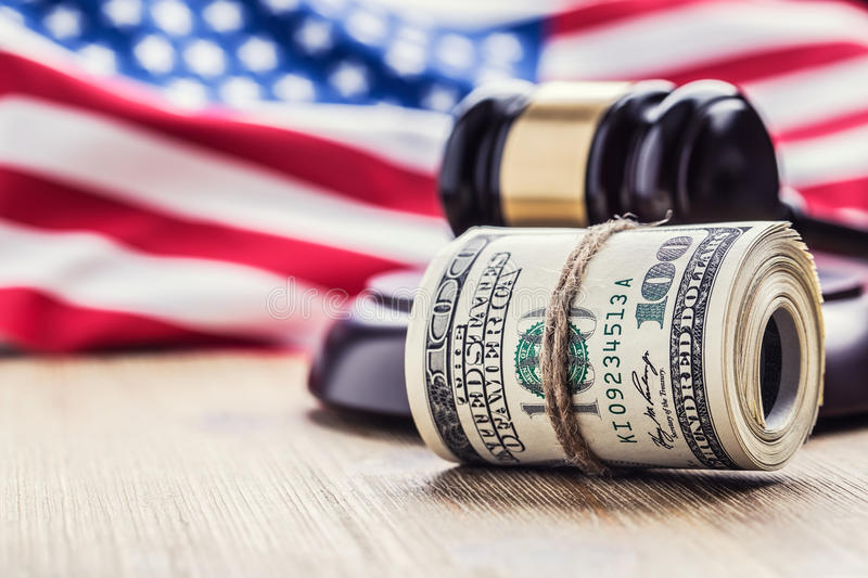 Judge`s hammer gavel. Justice dollars banknotes and usa flag in the background. Court gavel and rolled banknotes. Still life of a bribery, corruption in the US stock photography