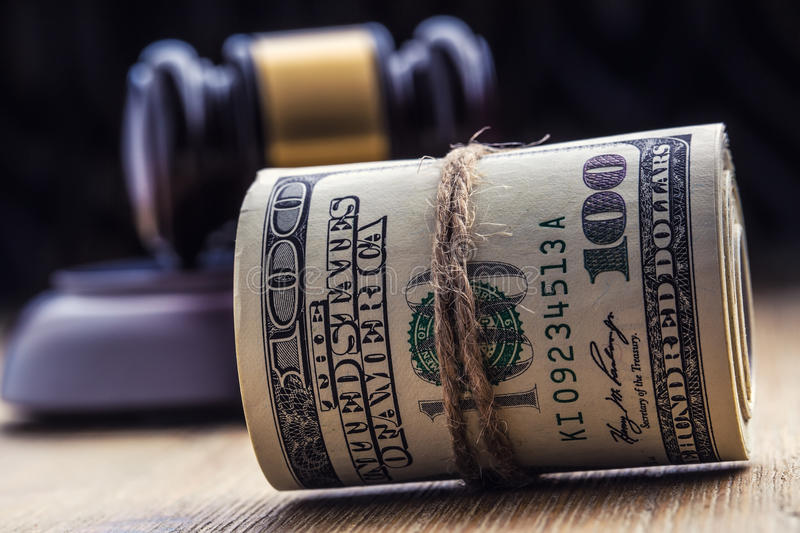 Judge`s hammer gavel. Justice dollars banknotes and usa flag in the background. Court gavel and rolled banknotes. Still life of a bribery, corruption in the US royalty free stock photography
