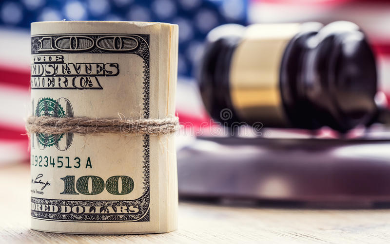 Judge`s hammer gavel. Justice dollars banknotes and usa flag in the background. Court gavel and rolled banknotes. Still life of a bribery, corruption in the US stock image