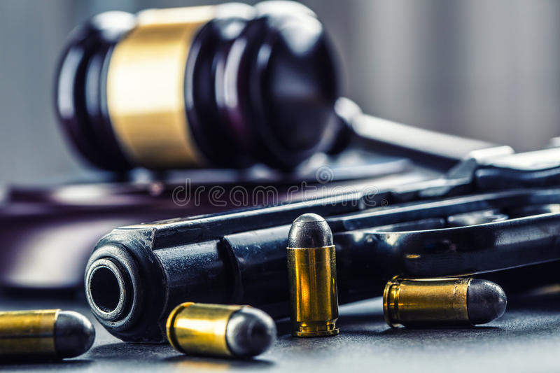 Judge's hammer gavel. Justice and gun. Justice and the judiciary in the unlawful use of of weapons. Judgment in murder.  stock image