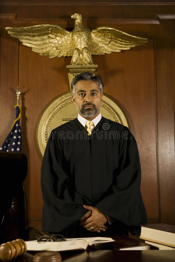 Judge Standing At Table In Court Room. Portrait of middle age male judge standing at table in court room royalty free stock photos