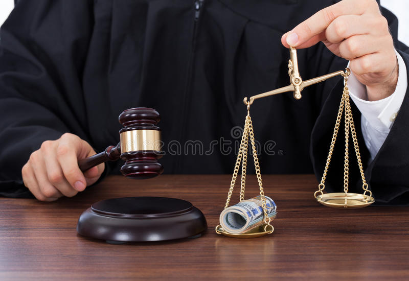 Judge striking gavel while holding scale with money stock photography