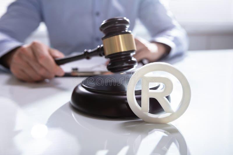 Judge Striking Mallet On Trademark Symbol. Close-up Of Judge Striking Mallet On Trademark Copyright Symbol stock photos